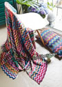Разноцветные плед и подушка с узором зигзаг. Спицы