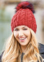 Красная теплая шапка с косами и меховым помпоном. Спицы